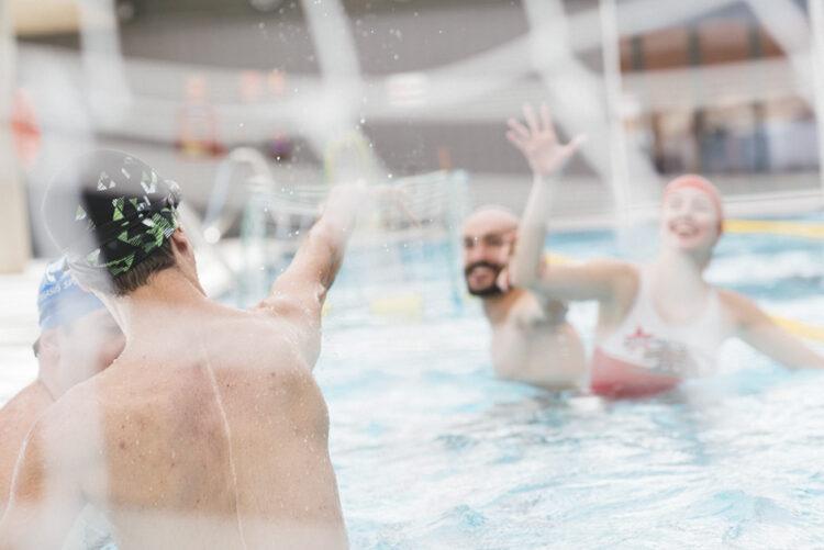 Profesor y alumnos de natación sonrien